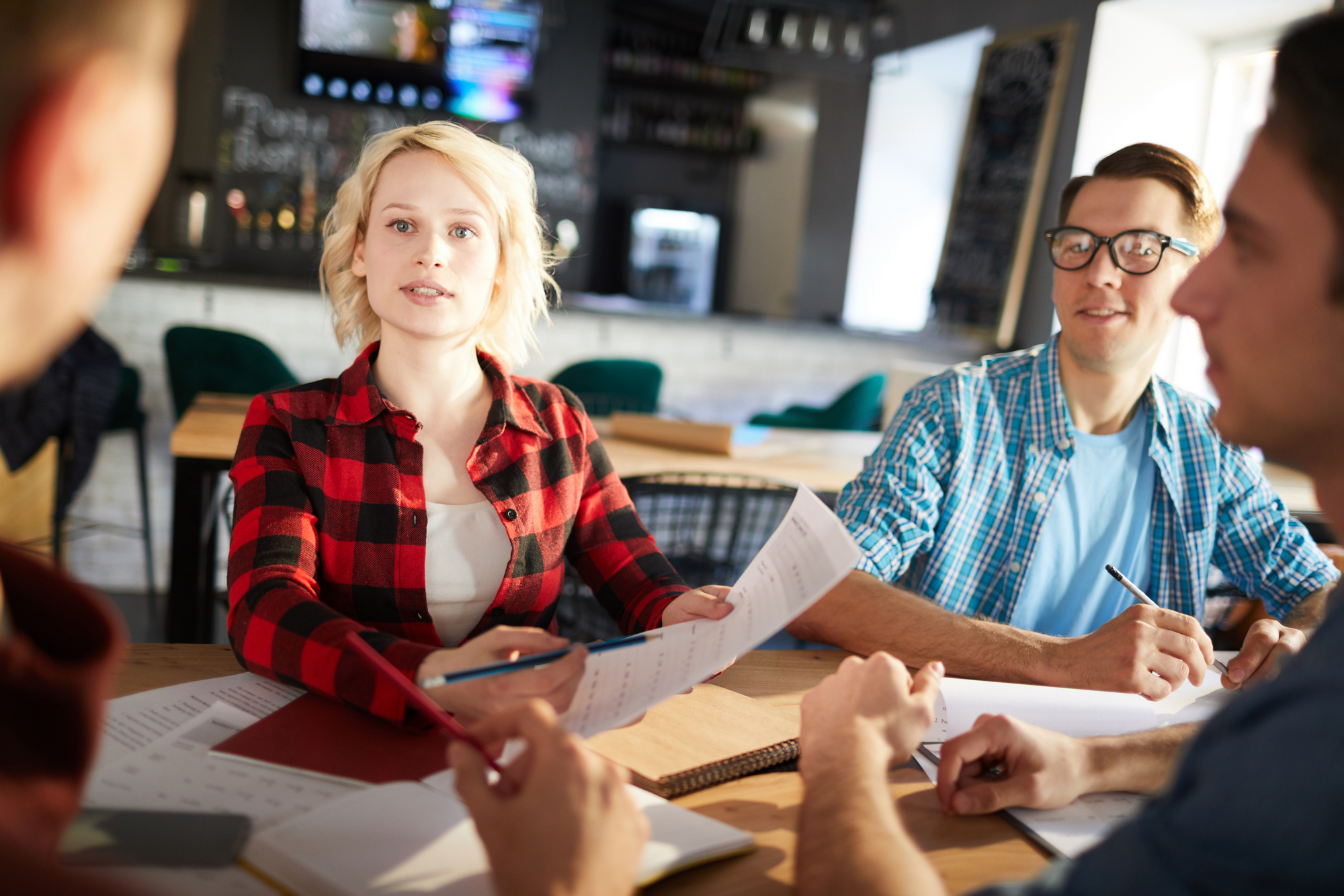 Group of young business professionals discussing ideas while collaborating on startup project during meeting in modern office, focus on blonde young woman pointing at document