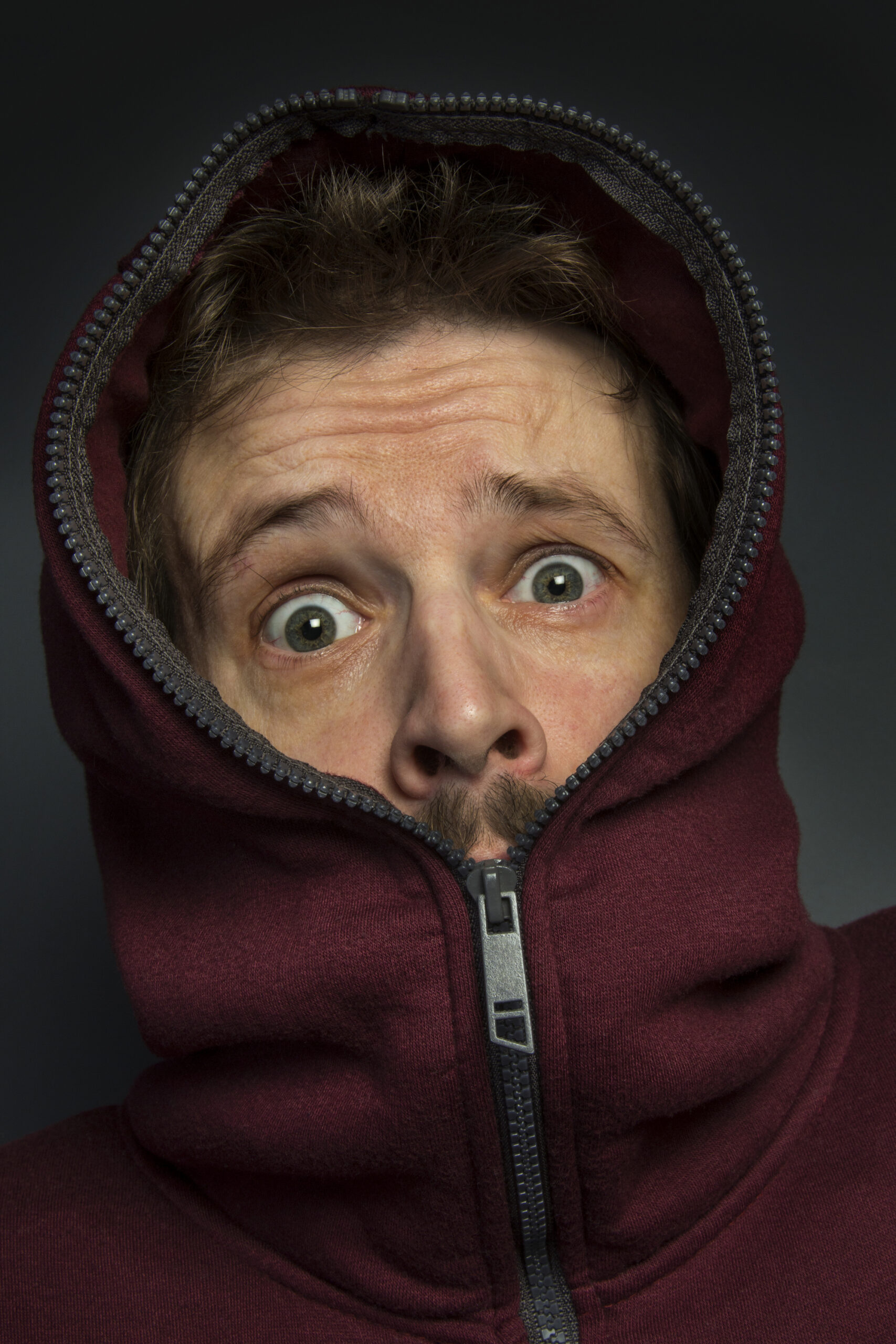 Man in hoody with a look of fear and surprise on his face.