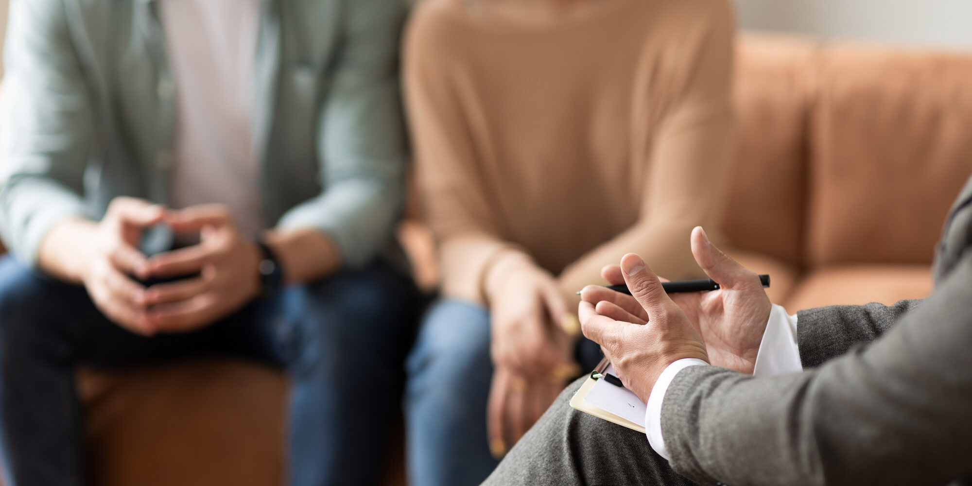 Help Concept. Closeup Cropped View Of Male Counselor Therapist Or Consultant In Suit Talking With Couple Sitting In Office, Giving Professional Advice. Selective Focus On Hands With Clipboard And Pen