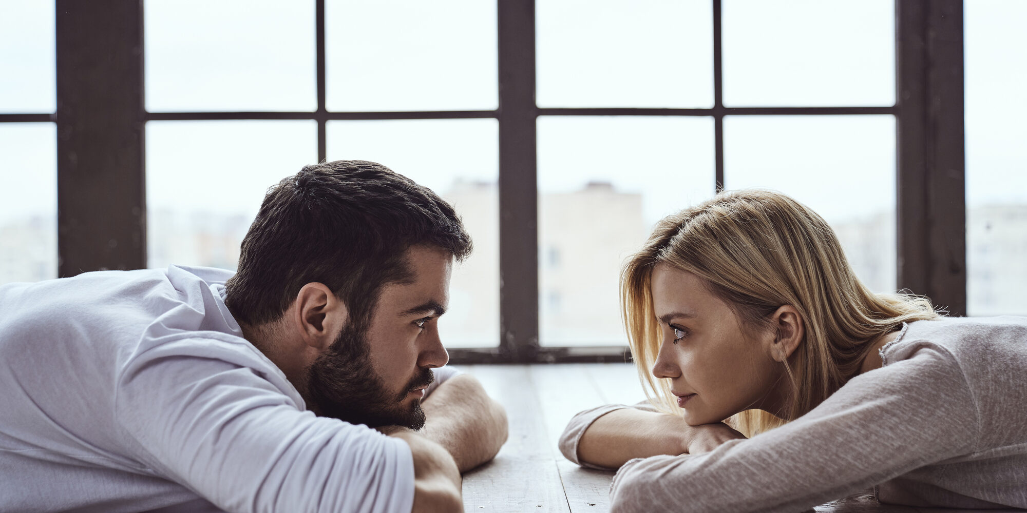 Young happy loving couple guy and girl lying against each other in front of big panoramic window and looking at each other