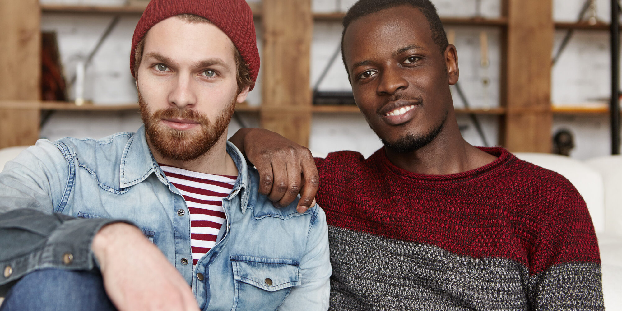 Homosexual love and relationships concept. Interracial gay couple relaxing at cafe: African-American man in sweater holding hand on his stylish bearded Caucasian boyfriend's shoulder in trendy hat