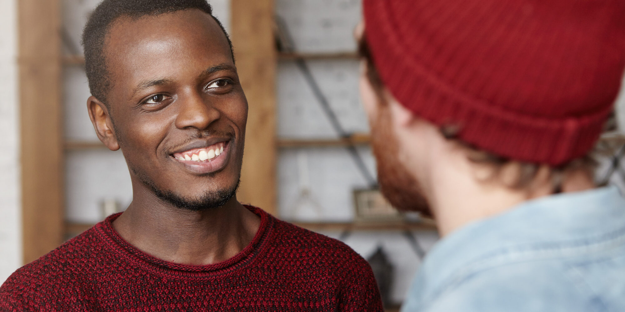 People, interracial friendship and communication concept. Handsome cheerful young Afro-American man dressed in cozy sweater smiling happily rejoicing at that his Caucasian friend got married
